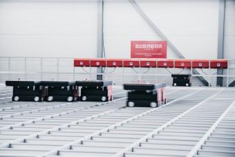 Roboty AutoStore poruszają się po kracie w magazynie