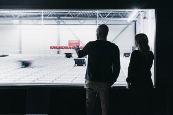 Pracownicy przyglądają się robotom systemu AutoStore w magazynie