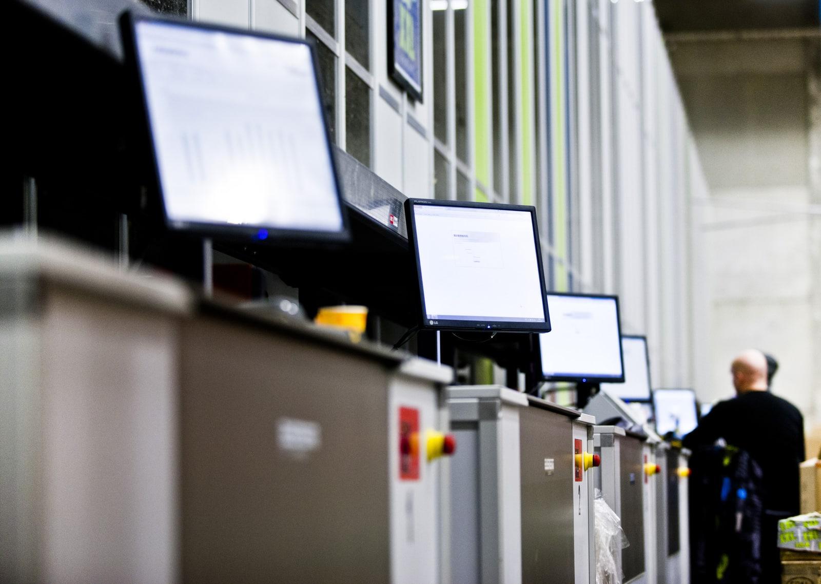 Ekrany komputerów w magazynie XXL i pracownicy magazynu