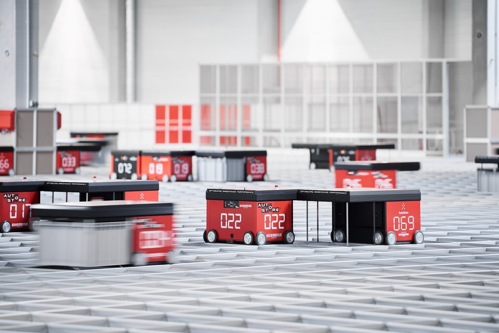 Kilka robotów AutoStore z linii czerwonej porusza się po kracie