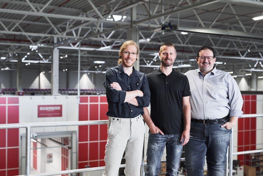 Thomas Klein i Ronny Höhn z Bergfreunde i Michael Kawalier z Element Logic i front of AutoStore grid