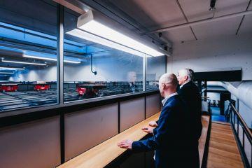 Jan Kleven i Roger Furnes obserwują pracę robotów AutoStore na kratownicy.