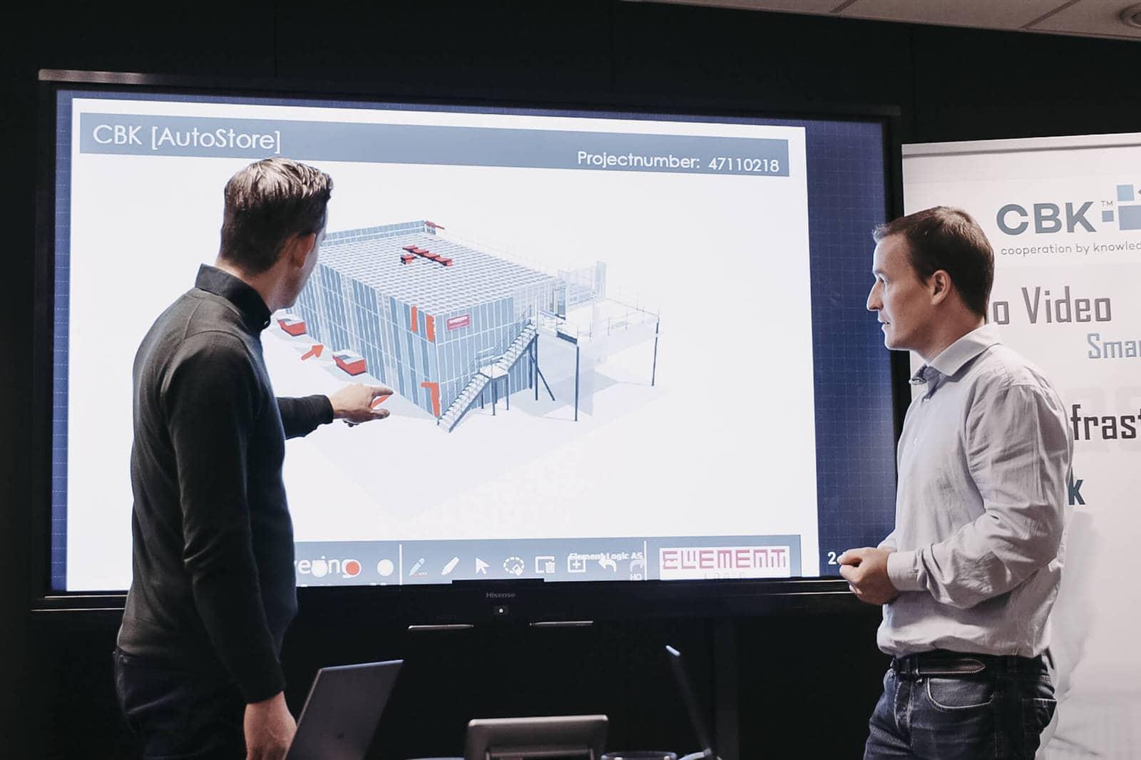 Dwóch mężczyzn wskazuje i patrzy na prezentację rysunku rozwiązania AutoStore.