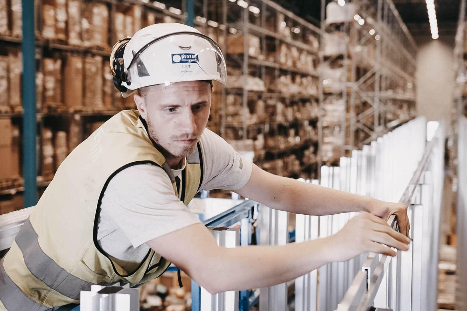 Mężczyzna w kasku i żółtej kamizelce buduje siatkę AutoStore przy użyciu aluminiowych kolumn.