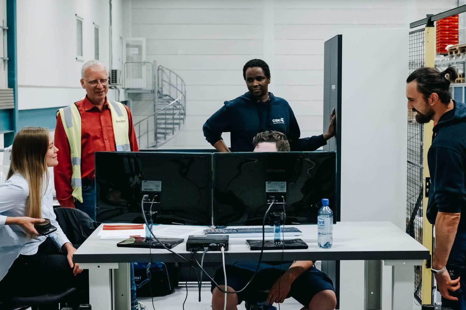 Pięć osób pracuje razem przed komputerem, ucząc się obsługi systemu AutoStore.