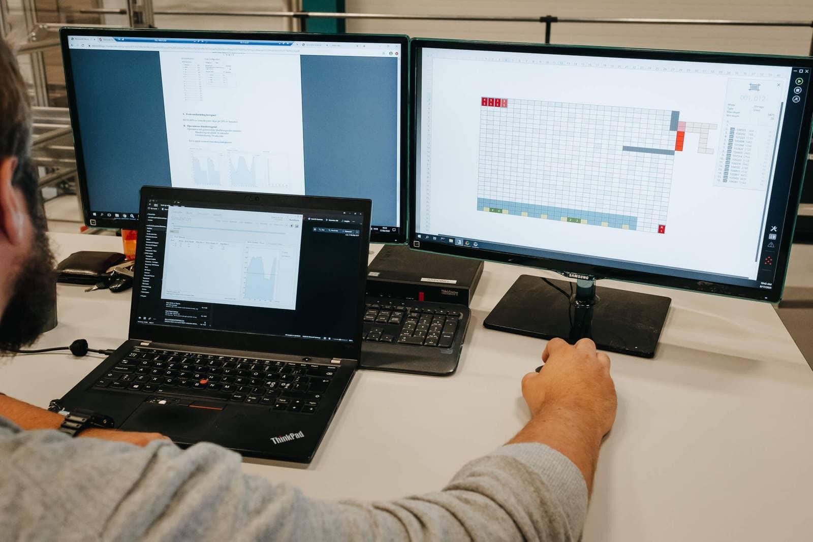 Mężczyzna pracujący przy AutoStore przy trzech ekranach komputerowych.