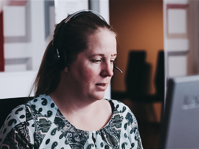Zbliżenie na kobietę rozmawiającą przez słuchawki przy komputerze.