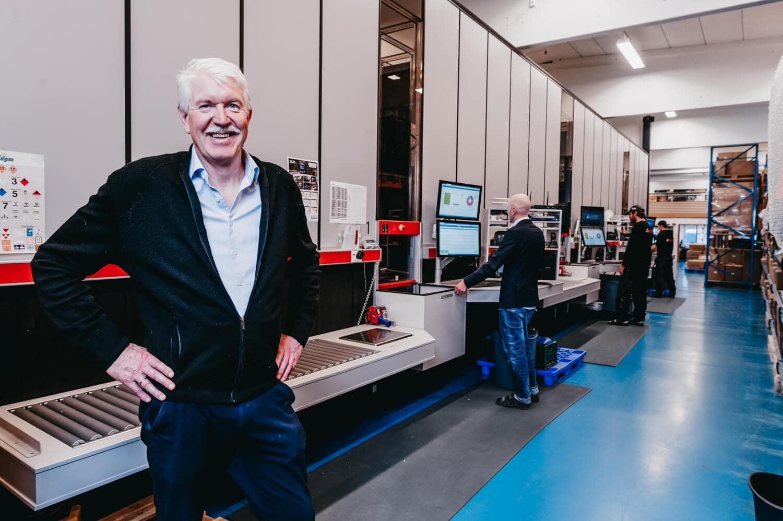 Dyrektor zarządzający, Jan Kleven, z dumą uśmiecha się do zdjęcia; w tle widoczne rozwiązanie AutoStore firmy Elotec i pracownicy obsługujący porty.
