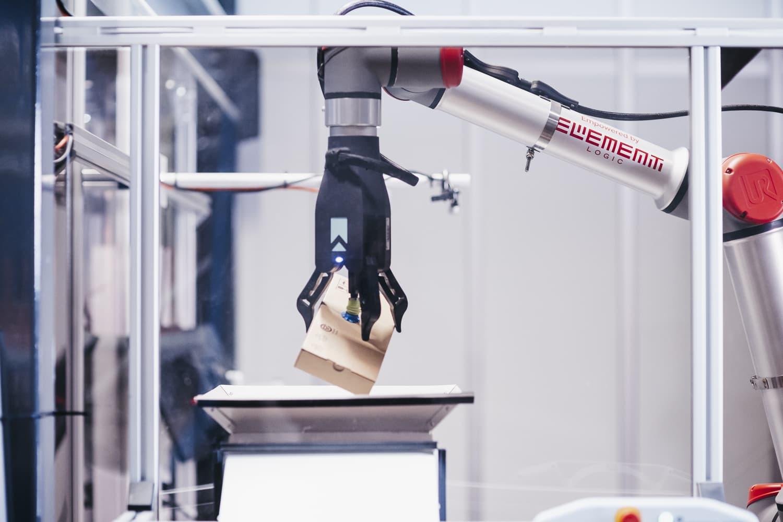 Ramię robota odbierające brązowe pudełko z AutoStore