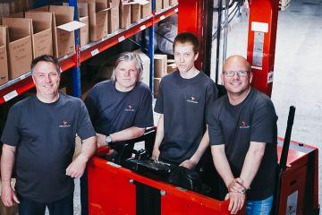 Czterech pracowników Colliflow stoi w magazynie i uśmiecha się do kamery.